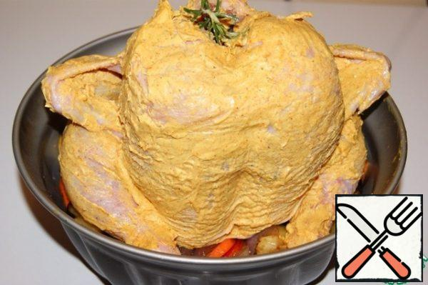 Hands gently separate the skin of the chicken in the breast area and lubricate the inside with fragrant oil. Then generously, from all sides cover the entire carcass with fragrant oil, stick inside through the neck of rosemary and plant on top of the pipe.