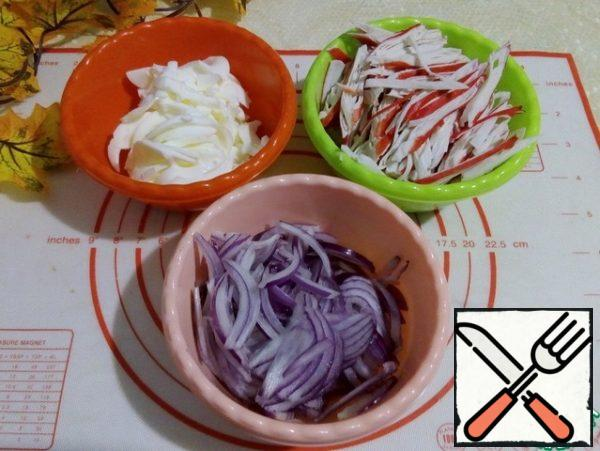 Boiled egg whites cut into strips. Crab sticks in oblique-a long straw. Onion cut into half rings.