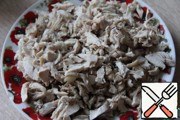 Boiled chicken (it is better to take not only the breast, but also the thighs, so that there is no dry meat) to break into fibers or finely chop.