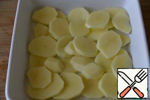 Peel the potatoes and cut into thin circles, so that he had time to prepare. Take the form, grease with oil, put the potatoes.