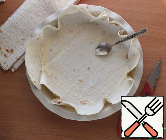 Thin pita bread cut to the size of the form into 4 parts. Form grease with oil, put a sheet of lavash, lubricate it finely with oil - and to do so with the remaining sheets of lavash. The edges of the pita bread should not protrude much beyond the shape, trim them and moisten with a brush with water, so as not to burn when baking.