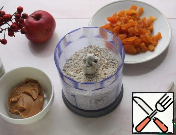 In the bowl of a blender, grind the oatmeal into a coarse crumb. Cut the dried apricots into pieces, add to the flakes and once again punch with a blender.