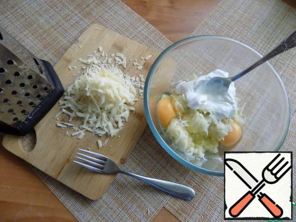 Break the eggs, put sour cream. Stir with a fork. Grate the cheese on a medium grater.