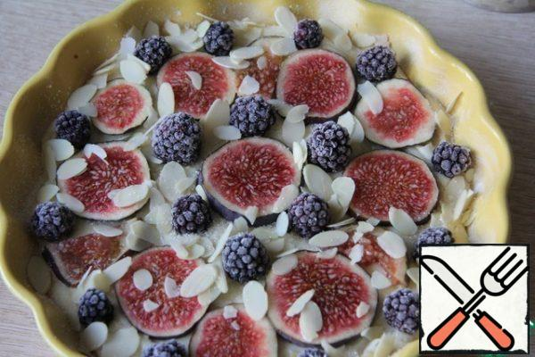 The form of grease and sprinkle with flour. Pour the dough, put the chopped figs and blackberries. Sprinkle with sugar and almond petals.