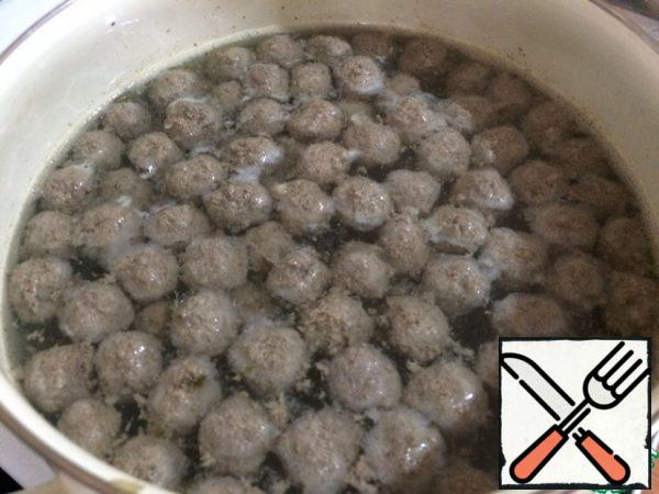 In boiling water, lower our meatballs. Very carefully remove the foam, which will be a lot. Now add the potatoes, salt, wait until it boils. Reduce the heat and cook.