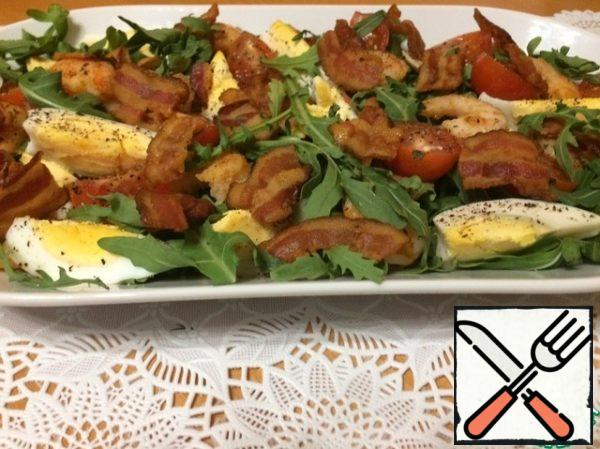 All, you can assemble the salad. Place the arugula, halved cherry tomatoes, shrimp, eggs, sliced into wedges and top with the bacon. Refuel right before eating.