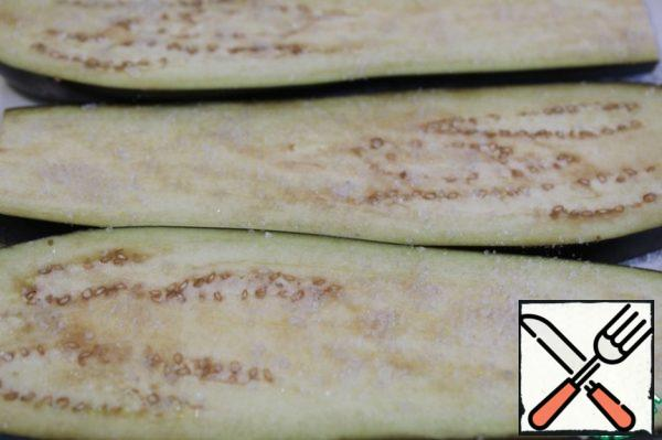 The eggplant cut off the tails, cut along the thickness of 3-5 mm, pour salt for 30 minutes.
