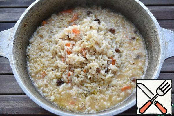 Next, fill the rice with raisins, gently pour in cold water and bring to a boil over high heat. When the water level reaches the rice level, gather the group from the edges to the center of the slide, reduce the fire to a minimum. Over rice posting a deep plate appropriate diameter, covering his, then kitchen a clean towel and entire pillar cover with a lid.