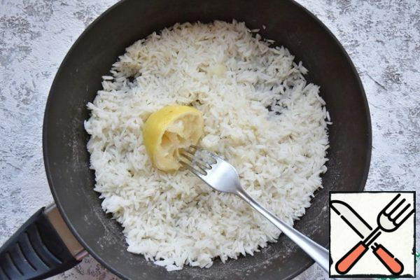 Cover the pan and leave the rice on medium heat for 10 minutes. At the end of time, the water will be absorbed into the rice completely. Turn off the heat and lightly loosen the rice with a fork. Squeeze the lemon pulp on top of the rice and stir into it.
