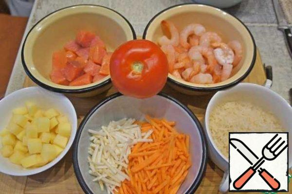 Prepare the products. Cut the fish into cubes, thaw the shrimp. Wash and clean the vegetables. Cut the potatoes into small cubes, chop the carrots and celery into strips. Wash the rice thoroughly.