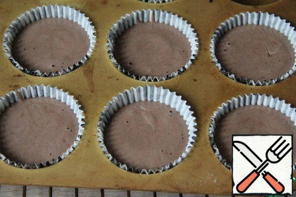 Put paper capsules for cupcakes in the form of Pour the dough, not reaching the edge of about 5 mm.