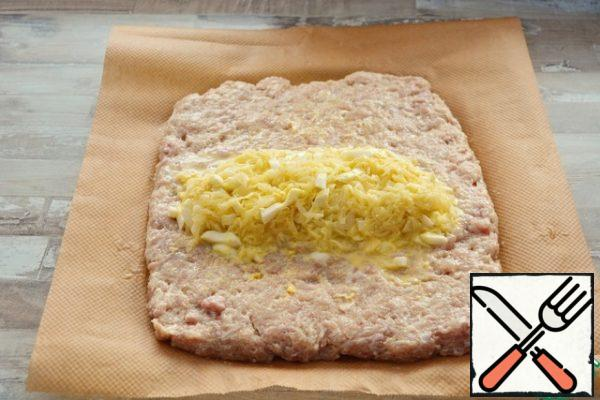 On a sheet of parchment spread out the minced meat, put the filling in the center. Hands slightly press it down.