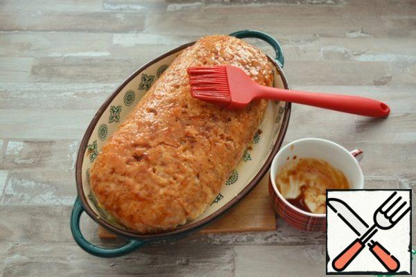 Prepare the frosting by mixing the ketchup and soy sauce. Brush the roll on top