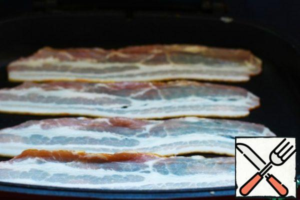 Wash the scallops. Put the strips of bacon in a dry pan and fry them to get a fragrant fat for the scallops.