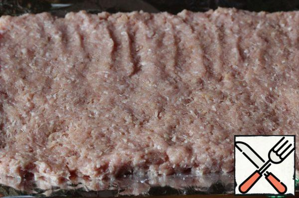 Put the minced meat on a double sheet of foil in the form of a long rectangle.