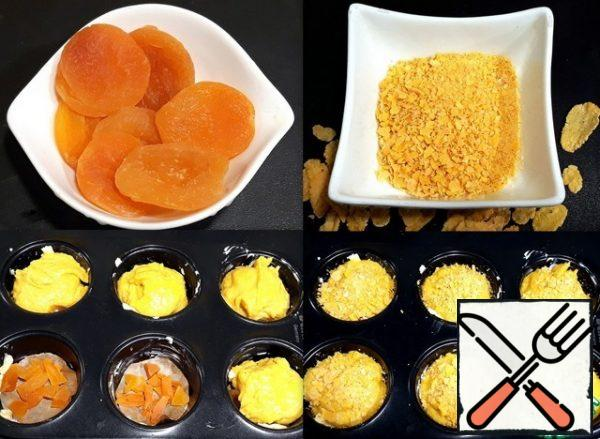 For the filling, I prepared dried apricots. She washed it, sliced and put on the bottom of the greased shape cells into circles cut from parchment paper. On dried apricots laid out the dough. On top of the dough sprinkled crushed corn flake.