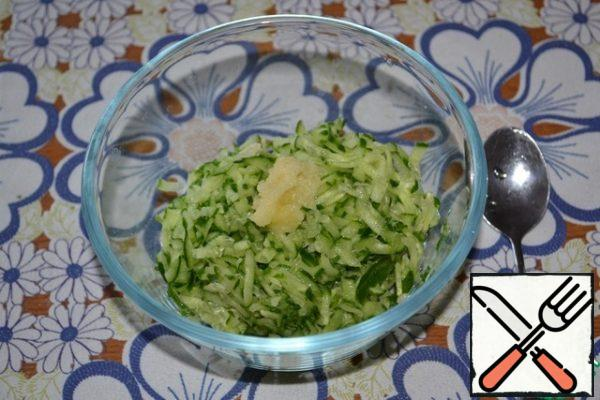 Grated cucumber squeeze from the juice, put it in a bowl. Add the squeezed garlic and lemon juice. Stir and remove for a while to the side.