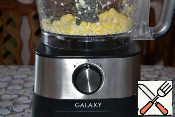 Grate the eggs on a large grater. And the food processor easily coped with this task.