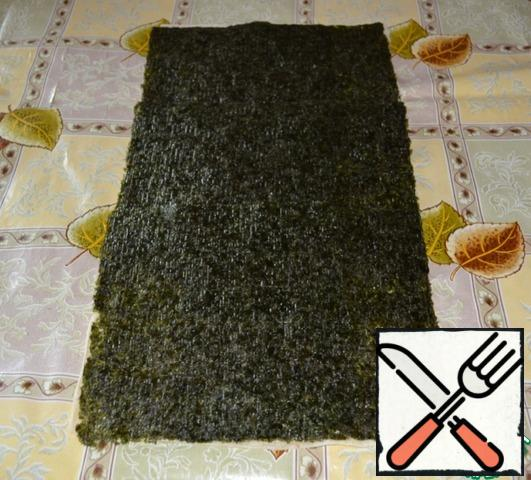 Flatten a sheet of pita bread on the table, cut off exactly the edges to get a rectangular layer. Top with overlapping sheets of nori.