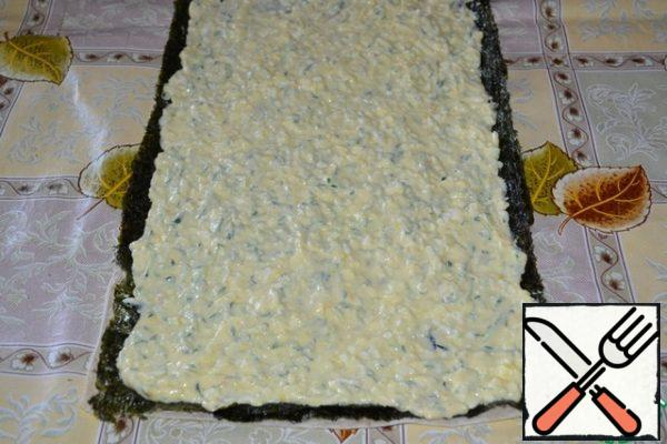 Carefully put on top of the nori cooked egg-cheese mass, not reaching the edge of 1 cm, smooth.