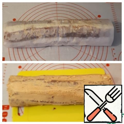 With the help of parchment, turn everything into a roll and put it in the freezer for 15 minutes, so that the cream will seize. At the end of time, take out the roll and cover it with cream.