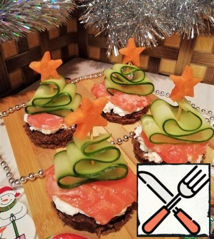On top of the cheese sandwich put the red fish. Using a toothpick from a cucumber, form a Christmas tree, decorate it with a star (cut from carrots). Set our Christmas tree in the middle of the sandwich.Bon appetit everyone!