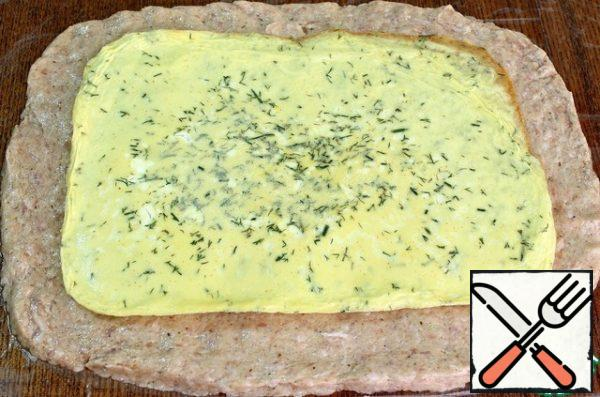 Sprinkle the table with water, put a plastic wrap (or cellophane bag) and put the minced meat on it in an even layer in the form of a rectangle. Put the omelet on the minced meat (you can sprinkle it with cheese) and use the film to roll it up.