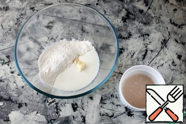 In a bowl, sift 100 g of flour, add salt, butter, kefir (warm) and yeast solution.