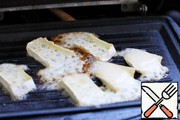 Pieces of brie cheese to fry on a dry grill.