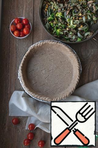 Roll out the dough between two sheets of baking paper. A baking pan covered with foil or grease with butter. Put the dough in the form, cut off the excess at the edges, pinch the sides, poke the bottom with a fork.