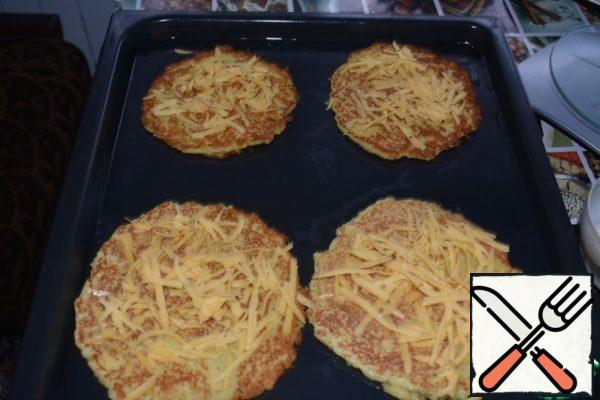 Set the oven to 180 gr. Spread on a baking sheet, greased with vegetable oil, pancakes. Each pancake pour the meat juice from the roast meat. Sprinkle them with 1/2 of the cheese.