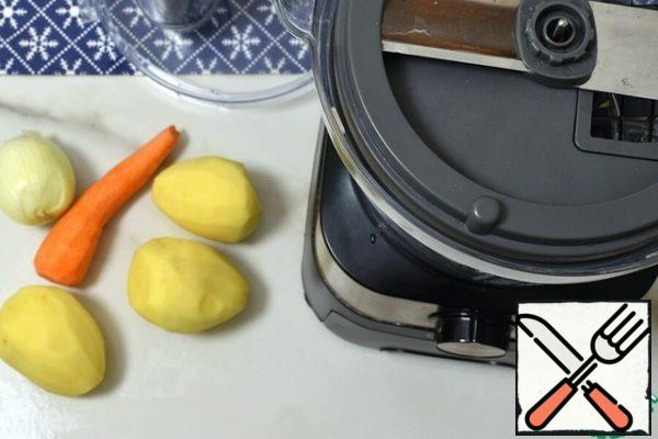 Wash and clean the vegetables. Install the nozzle for cutting cubes. Slice the potatoes, put them in a microwave-safe dish, and cover with cold water. Drain and fill with fresh water.