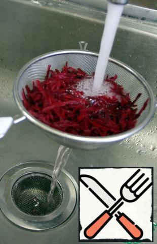 Put the grated beets in a sieve and rinse well in cold water so that the salad does not turn beet red later.