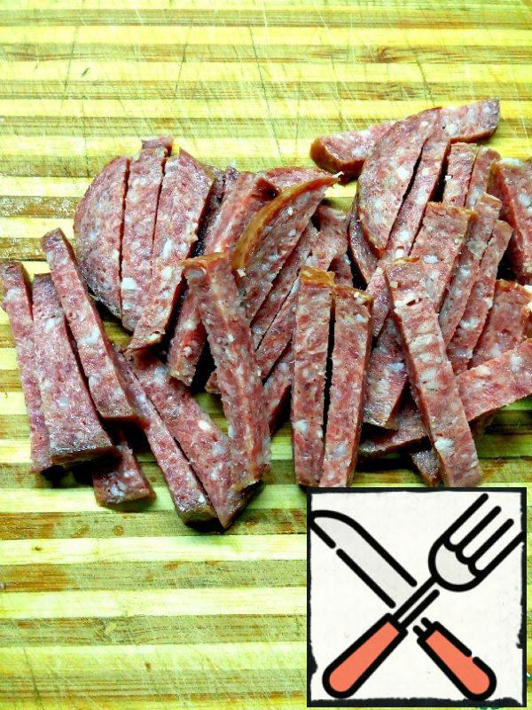 Cut the sausage into strips. To prepare this salad, you can use sausages such as salami or Servelat. In order for the salad to be more spicy, you can add raw smoked sausage along with semi-smoked sausage.