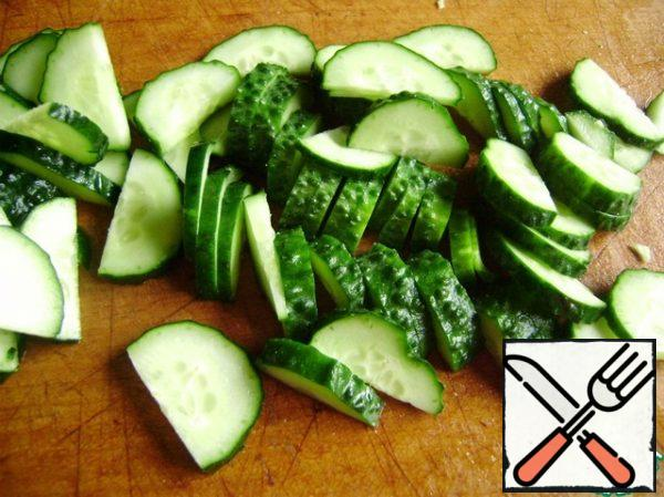 Cucumbers cut into half rings. Add to the cabbage.