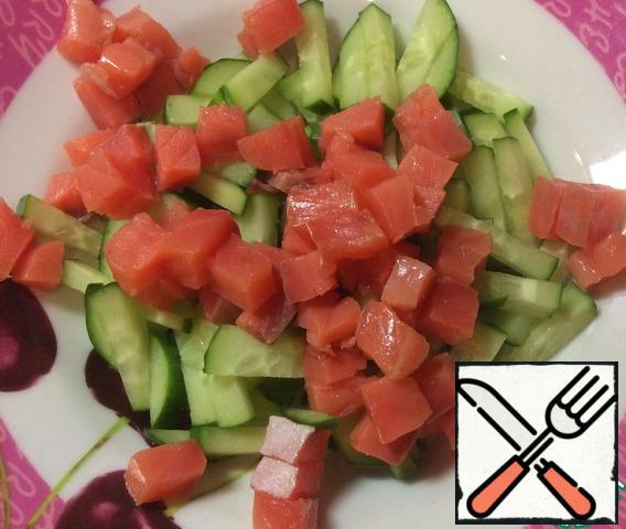 Cut the salmon into cubes and add to the sliced cucumber.