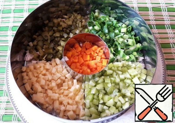 And spread around the sliced bell peppers, green onions, pickles and cheese.