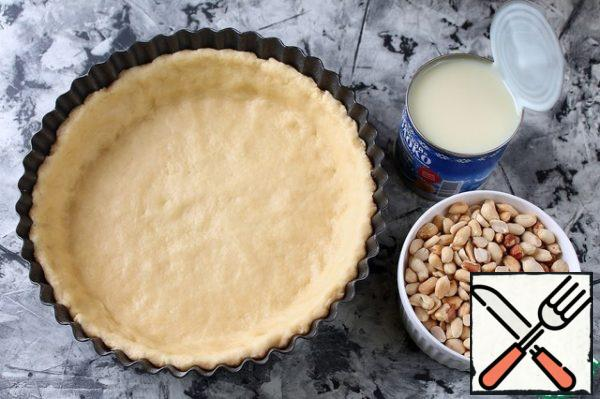 Fry the peanuts and peel them. Put the peanuts on the dough, add salt and pour the condensed milk on top.
