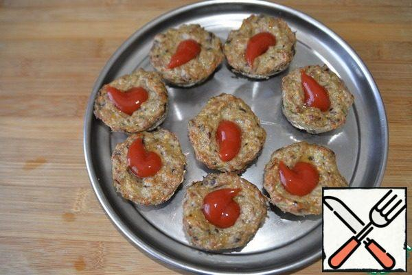 We get the ready-made meat base. In the middle of each billet, put half a tablespoon of tomato ketchup.