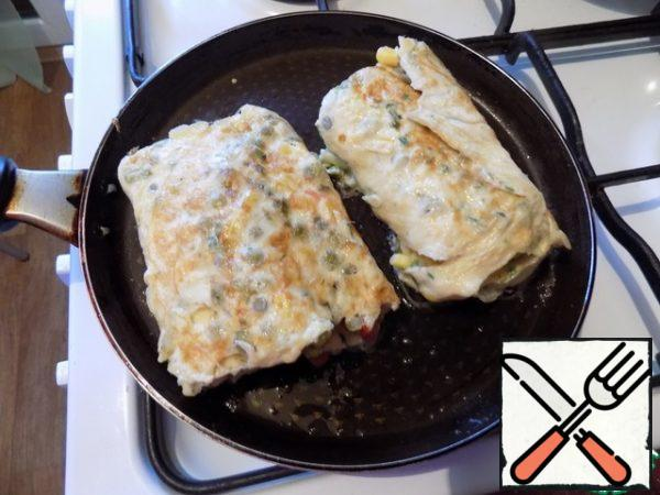 When it was completely twisted, for convenience, I cut it in half. So it is more convenient to finish it until ready. Reduce the heat to a minimum, cover with a lid and fry the omelet to a beautiful color on both sides, turning it over a couple of times.