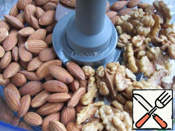 "Prepare the base for the cake. Place the almonds and walnuts in the bowl of a food processor with the ""chopping Knife"" attachment."