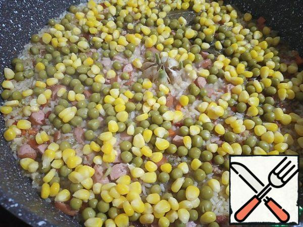 After the water boils a little - it will almost not be over the rice, pour the peas and corn on top.