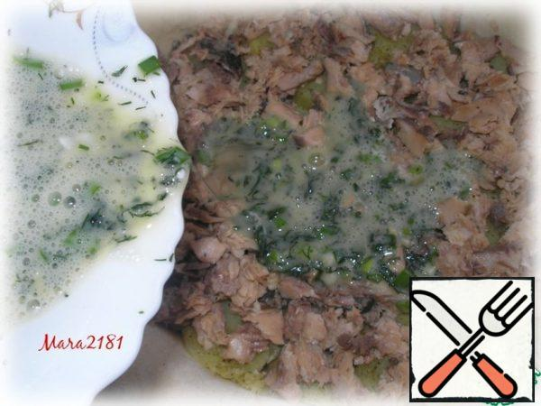 Next, put a layer of canned pink salmon (pre-drain the liquid and remove the bones). In a separate container, beat 3 eggs, add salt, finely chopped dill and green onions (to taste), mix thoroughly. Pour the egg mixture evenly over the canned pink salmon.