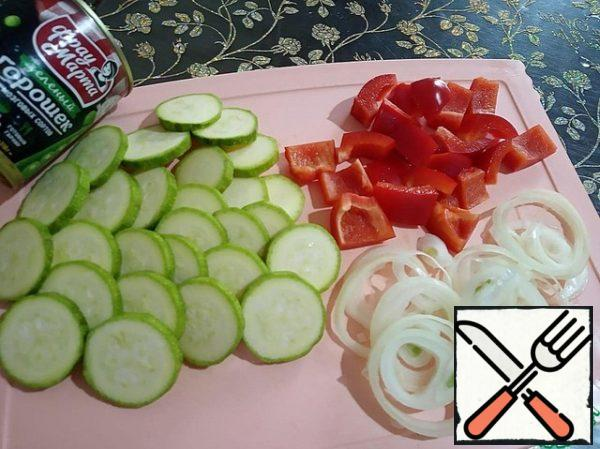 Peel the onion and cut it into rings. Zucchini cut into thin slices, wash and dry. Peppers are cleaned from seeds and cut into large pieces.