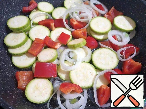 In a large frying pan, heat the olive oil and fry the peppers, zucchini and onions over high heat, stirring occasionally.