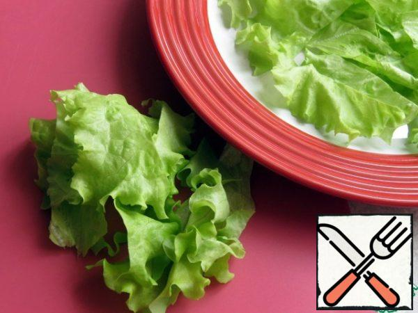 Tear the lettuce leaves or coarsely cut them and put them on a dish.