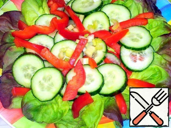 She spread the lettuce leaves on a large platter. Bell pepper cut into thin slices and put on the leaves. Cucumbers in circles and spread on top of the pepper. And so two layers.