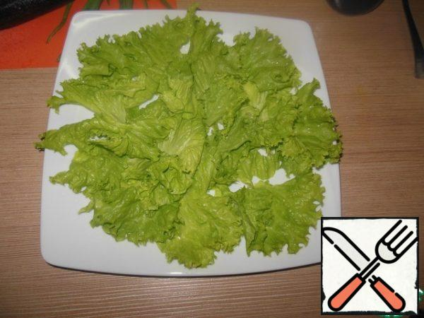 Put the lettuce leaves on the dish.