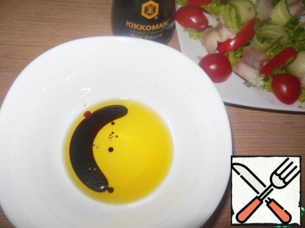 Let's prepare salad dressing. Mix the oil, soy sauce, and balsamic. And pour our salad.