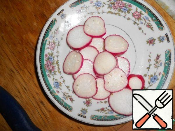Wash the radishes and cut them into thin slices.